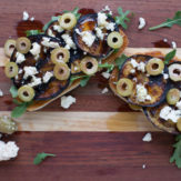 GRILLED EGGPLANT TARTINES WITH ARUGULA, FETA, GREEN OLIVES AND HONEY